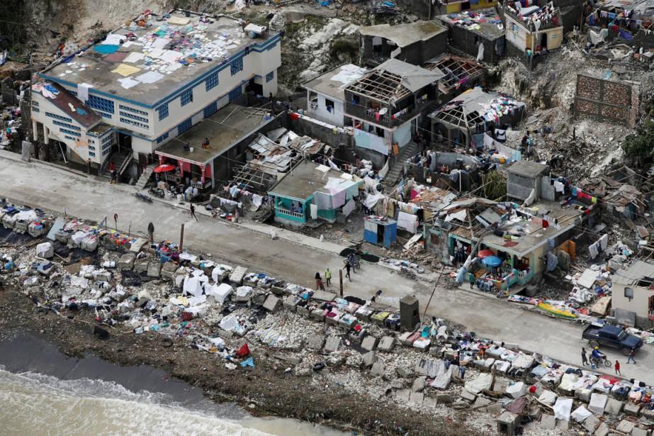 Des gens marchent à proximité de maisons détruites par le passage de <em>Matthew</em>, sur le littoral de Jérémie, le 6 octobre. (photo Carlos Garcia Rawlins, REUTERS)