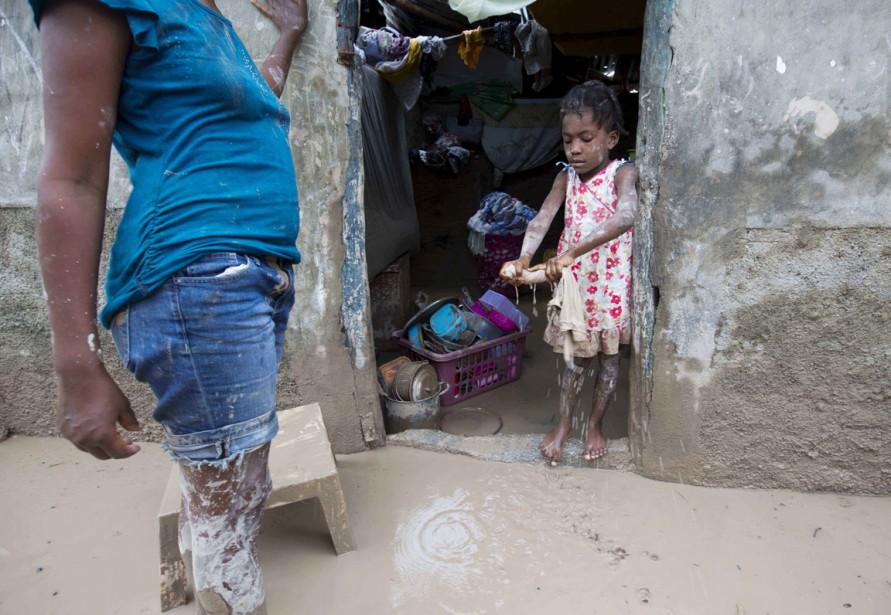 Une petite fille aide sa mère à retirer la boue laissée dans sa maison par le passage de <em>Matthew</em>, dans la ville des Cayes, située sur la péninsule de Tiburon, le 6 octobre. (photo Dieu Nalio Chery, AP)