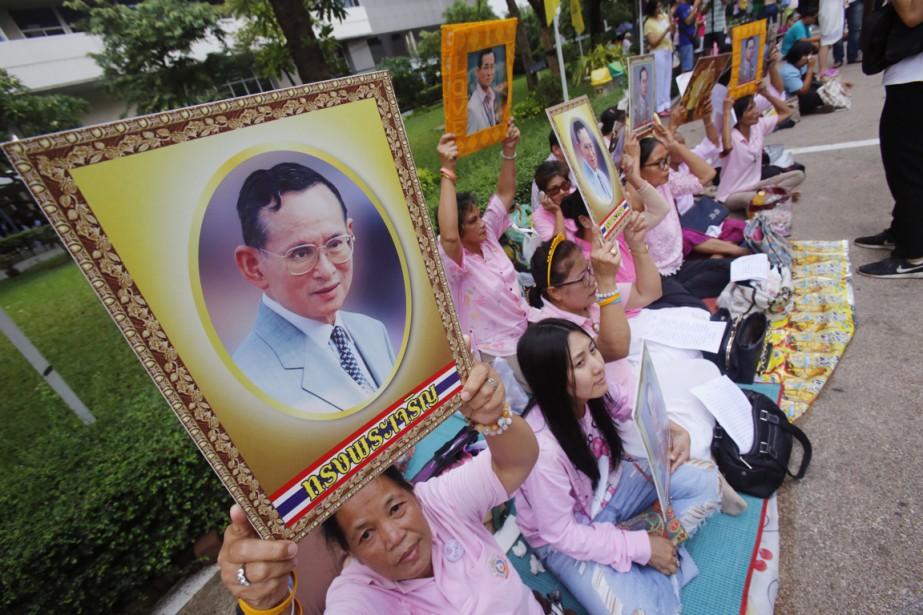 Des partisans prient devant l'hôpital Siriraj, alors que la santé du roi est de plus en plus chancelante, le 12 octobre. (photo Sakchai Lalit, AP)
