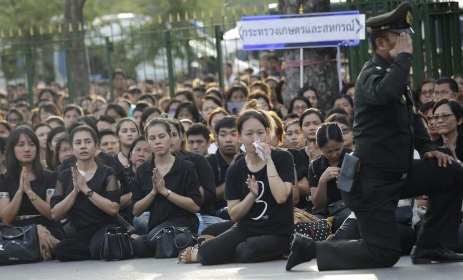 Un soldat salue, un genou au sol, le convoi transportant la dépouille du défunt souverain, à Bangkok, le 14 octobre. (photo Sakchai Lalit, AP)