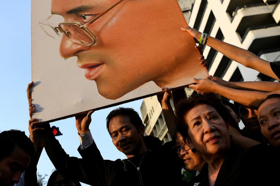 Des gens brandissent un portrait du roi Bhumibol Adulyadej, alors que la procession devant mener son corps vers le Grand Palais a lieu dans la capitale thaïlandaise. Des milliers de personnes sont descendues dans les rues de Bangkok pour rendre un dernier hommage au roi adulé. (photo MANAN VATSYAYANA, AFP)