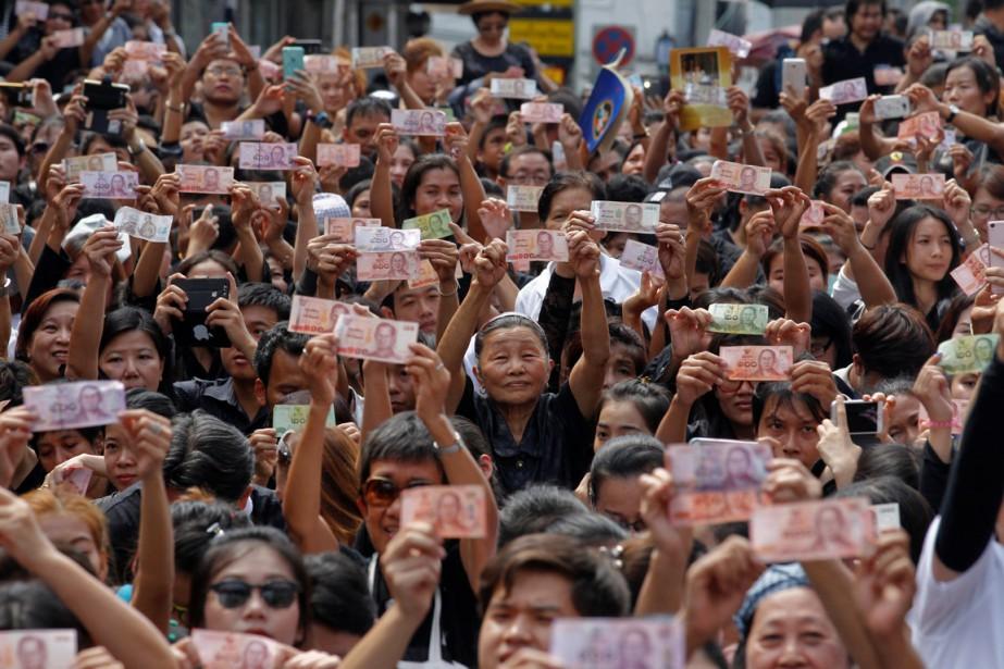 Ils étaient plusieurs à tenir des baths (monnaie thaïlandaise) en attendant le passage du convoi funeste menant le roi vers le Grand Palais, les billets affichant sur une face un portrait du souverain. (photo v, REUTERS)