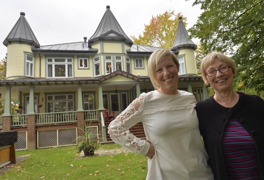 Vicky Chalifour et sa mère, Susan Tivendell, posent devant la façade de leur maison, qui est en réalité à l'arrière, face au fleuve. (Le Soleil, Patrice Laroche)