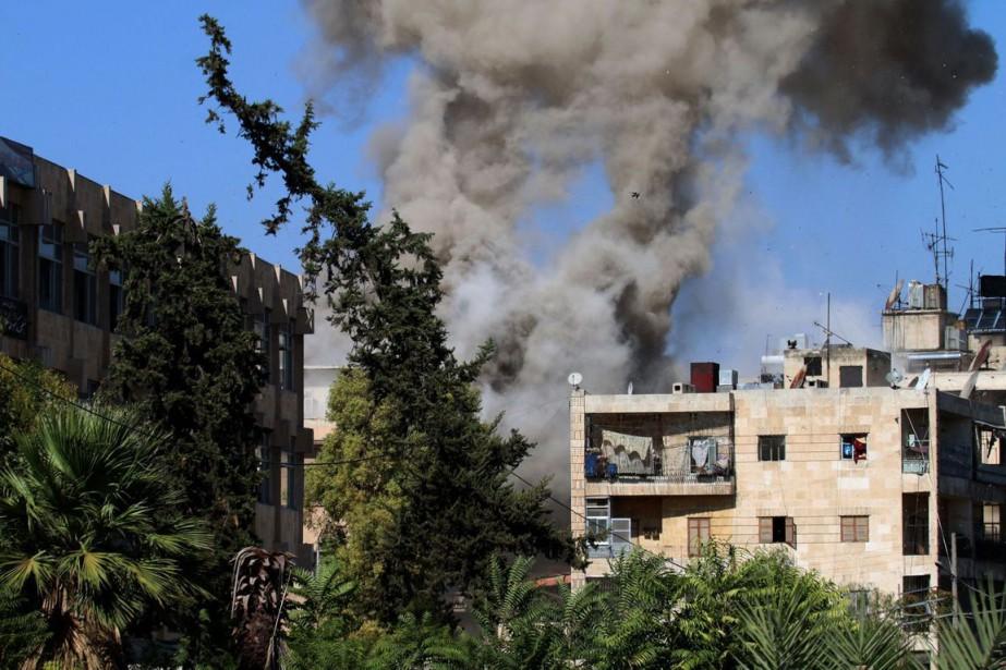 De la fumée s'échappe d'un immeuble d'un quartier... (Photo GEORGE OURFALIAN, AFP)