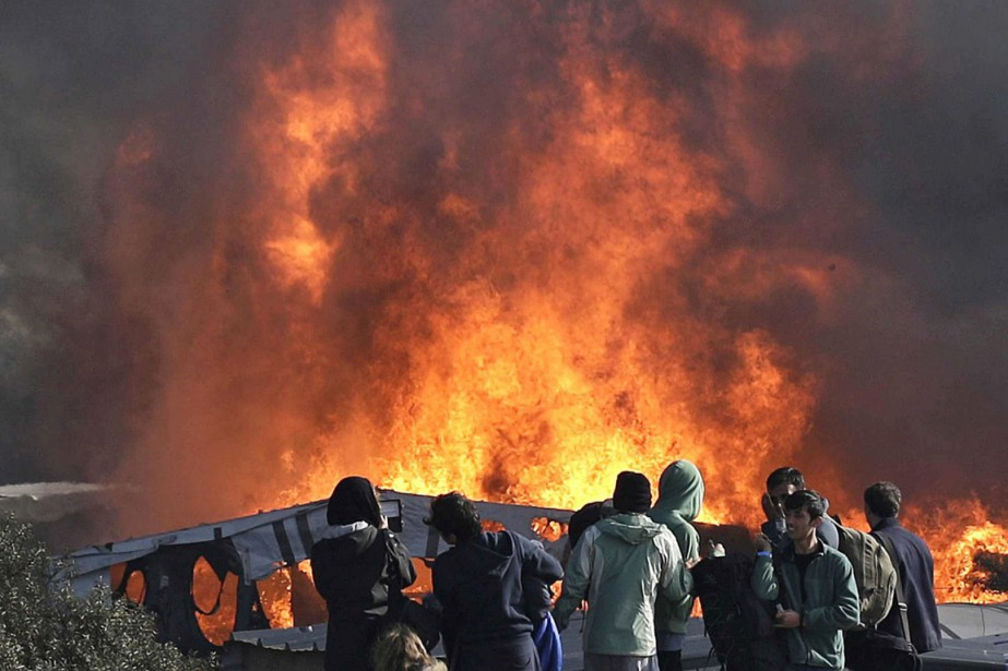 Thick smoke and flames rise from amidst the...