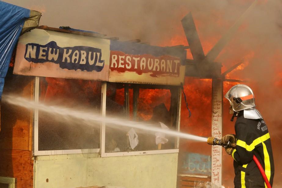 Un pompier s'affaire à éteindre les flammes qui ravagent ce petit restaurant afghan du camp, le Nouveau Kaboul. (photo François NASCIMBENI, AFP)