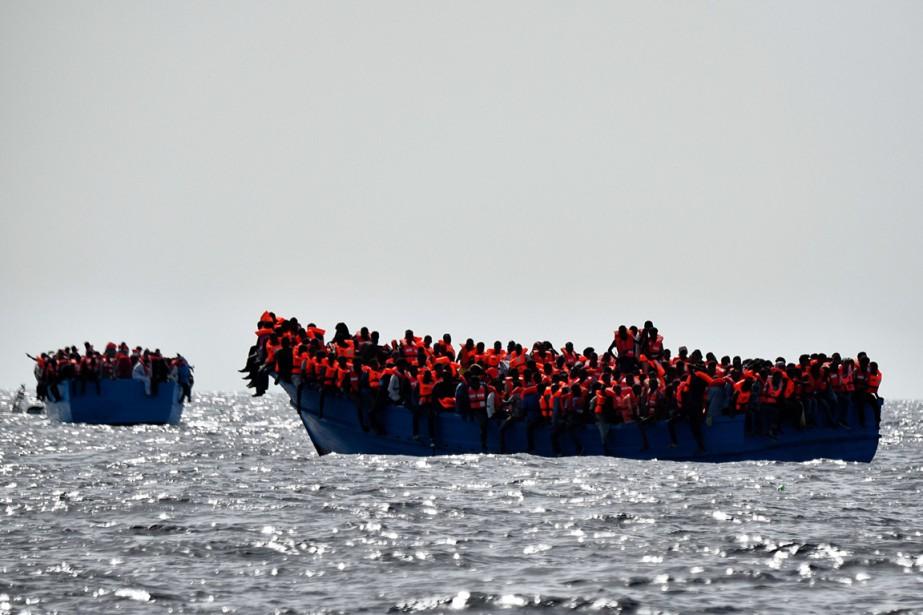 Des migrants attendent à bord d'embarcation d'être secourus,... (photo ARIS MESSINIS, archives AFP)