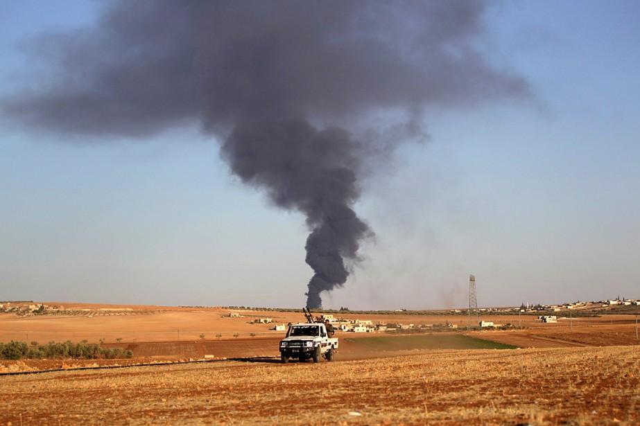 Des rebelles conduisent un véhicule sur une route... (PHOTO KHALIL ASHAWI, REUTERS)