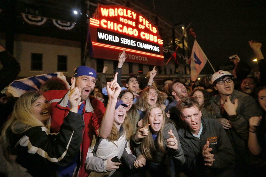 Chicago Cubs fans celebrate in front of Wrigley...