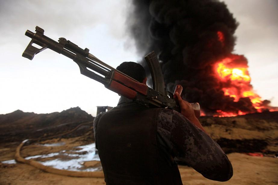 Un soldat irakien regarde un incendie allumé par... (Photo Alaa Al-Marjani, REUTERS)
