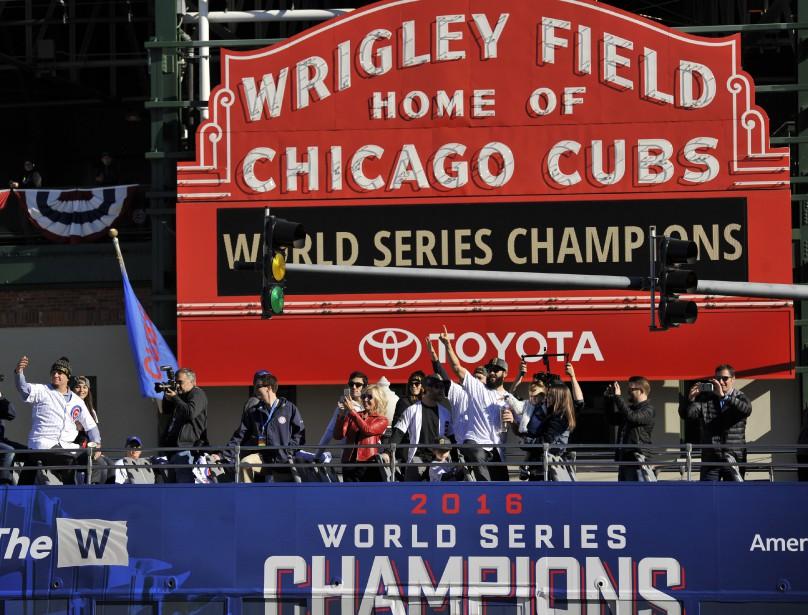 Les joueurs des Cubs Kyle Schwarber (à gauche) et Jake Arrieta (au centre)saluent la foule devant le Wrigley Field. (Photo Paul Beaty, AP)