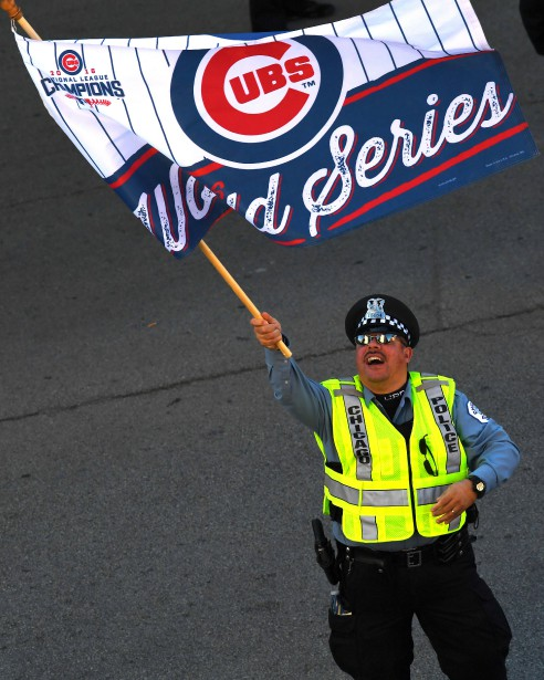 Un policier célèbre en brandissant un drapeau à l'effigie des Cubs près du Wrigley Field. (Photo Patrick Gorski, USA Today Sports)