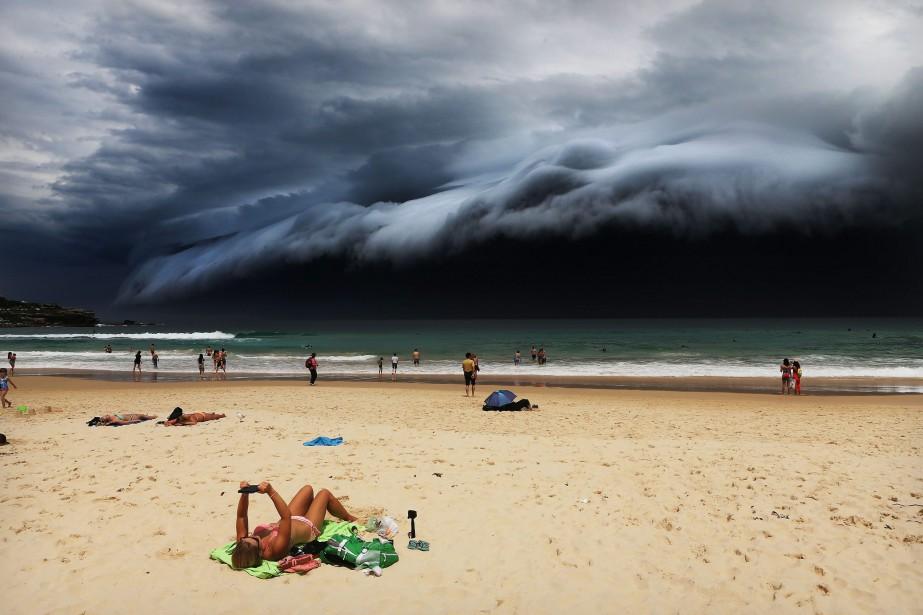 Cette photo présentant un «nuage tsunami» qui plane sur Sydney pendant qu'une touriste regarde sa tablette, inconsciente du nuage approchant sur la plage de Bondi a valu le premier prix Photos isolées, Nature à Rohan Kelly du Daily Telegraph. (Photo courtoisie, Rohan Kelly)