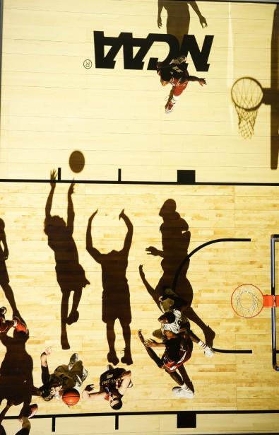 Greg Nelson des États-Unis offre une plongée au-dessus des joueurs de basketball en plein match où les ombres semblent faire office de joueurs supplémentaires. (Reproduction Le Progrès-Dimanche, Jeannot Lévesque)