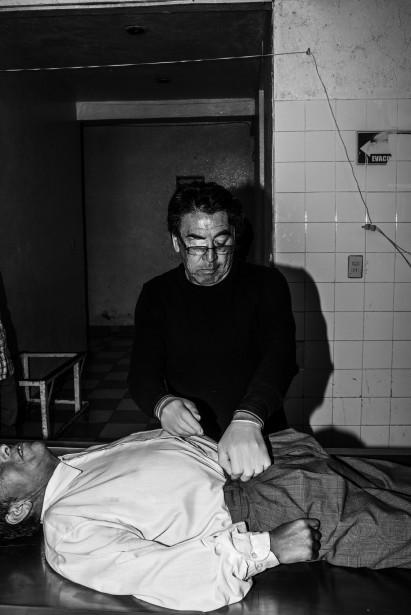 Un employé d'un centre funéraire habille un cadavre avant de le mettre dans un cercueil. Grâce à l'embaumement, le défunt est présenté comme s'il s'était paisiblement endormi. (Photo courtoisie, Sébastien Van Malleghem)