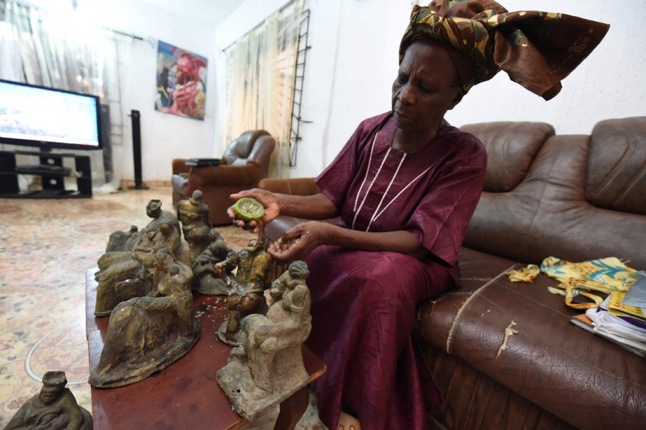 Elizabeth Olowu, 77 ans, frotte ses sculptures en... (PHOTO AFP)