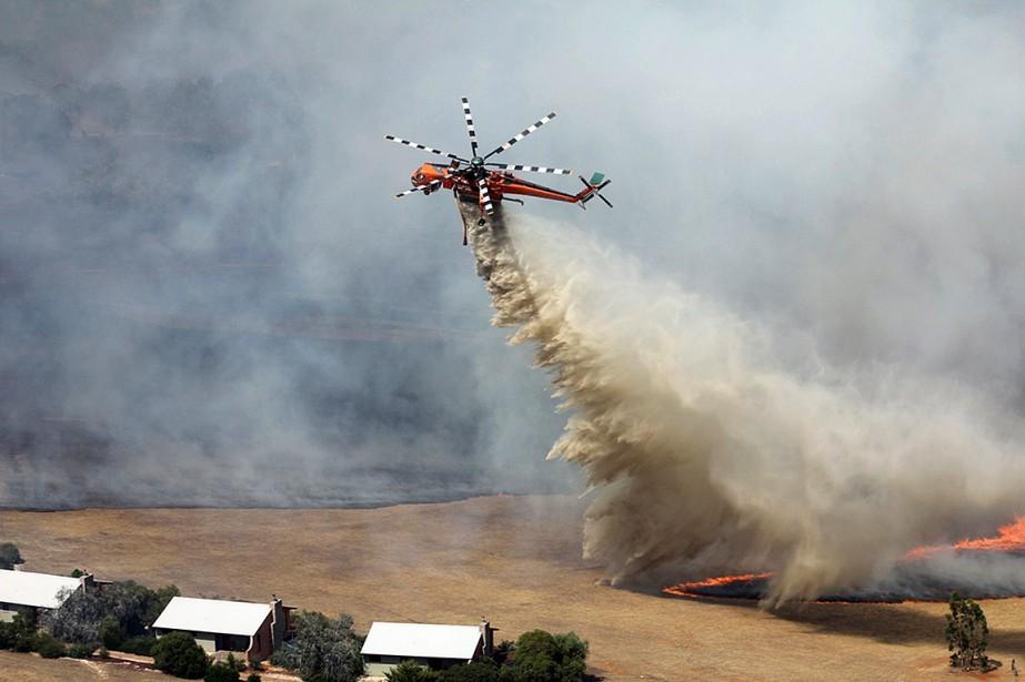 Un hélicoptère lutte contre un feu en Australie... (REUTERS)