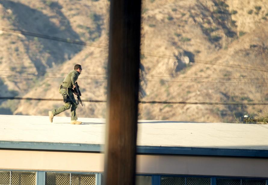 Un tireur d'élite de l'équipe SWAT marche sur le toit d'un gymnase alors qu'un suspect qui a tiré sur plusieurs personnes est barricadé près d'un bureau de vote en Californie. (AP)