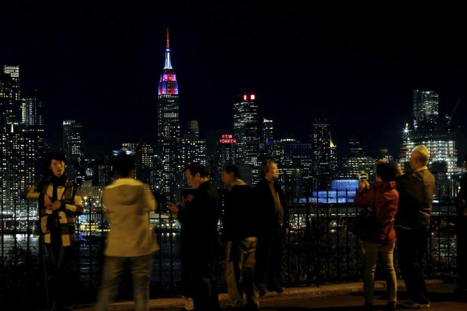 Des gens se tiennent sur la rive de Weehawken, au New Jersey, où ils peuvent voir l'Empire State Building s'illuminer en rouge, bleu et blanc à New York. (AFP)
