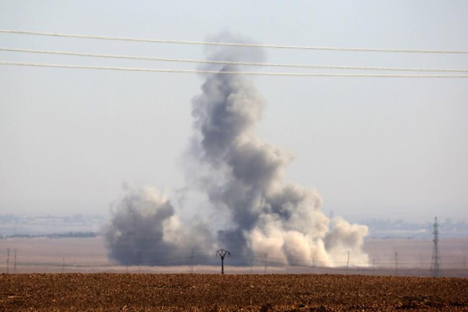 Ci-dessus, une colonne de fumée s'élève du village... (photo DELIL SOULEIMAN, archives AFP)