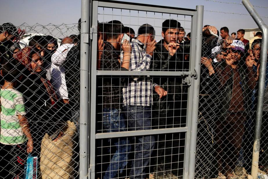 Des gens se massent à la clôture entourant... (photo Zohra Bensemra, REUTERS)