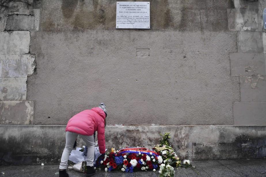 Une femme dépose des fleurs sous une des plaques commémoratives dévoilées dimanche, un an jour pour jour après les attaques. (AFP, Philippe Lopez)