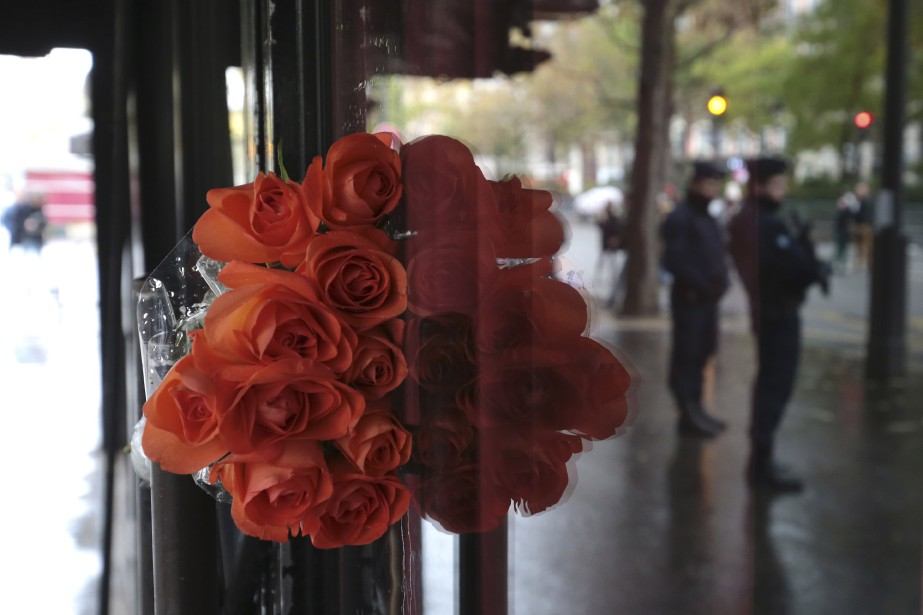 Le reflet de policiers dans la vitrine du Bataclan apparait à côté d'un bouquet de roses rouges. (AFP)