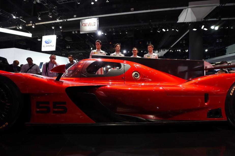 Les coureurs de l'écurie Mazda posent derrière la voiture de courseMazda RT24-P DPi, juste après son dévoilement. (AFP)
