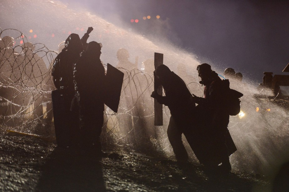 Police use a water cannon on protesters during...