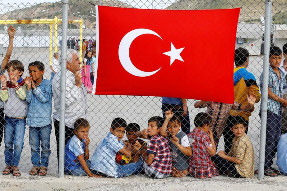 Des réfugiés attendent l'arrivée imminente de responsables gouvernementaux... (photo Umit Bektas, archives REUTERS)