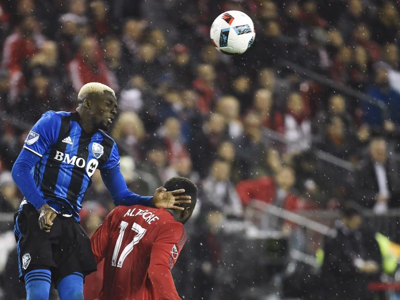 Ambroise Oyongo fait une tête alors qu'il joue du coude avec Jozy Altidore. (Photo Nathan Denette, La Presse canadienne)