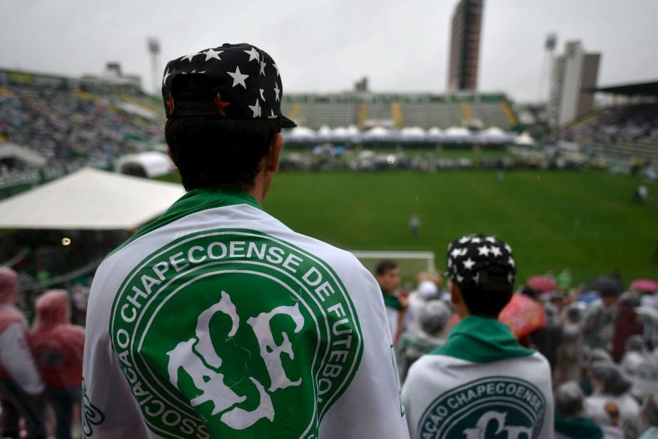 Les gens assemblés dans le stade attendent le cortège funéraire. (AFP)