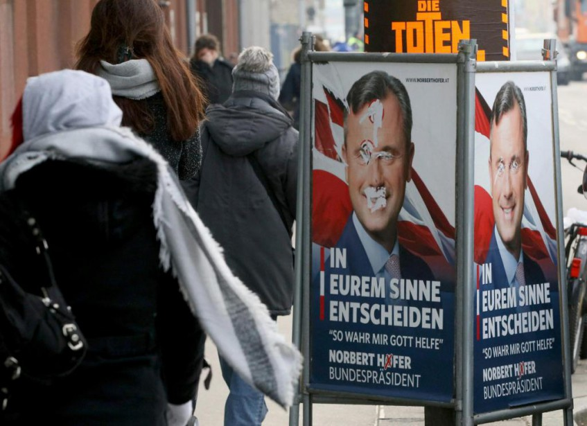 Des passants déambulent devant une affiche de Norbert... (PHOTO RONALD ZAK, ASSOCIATED PRESS)