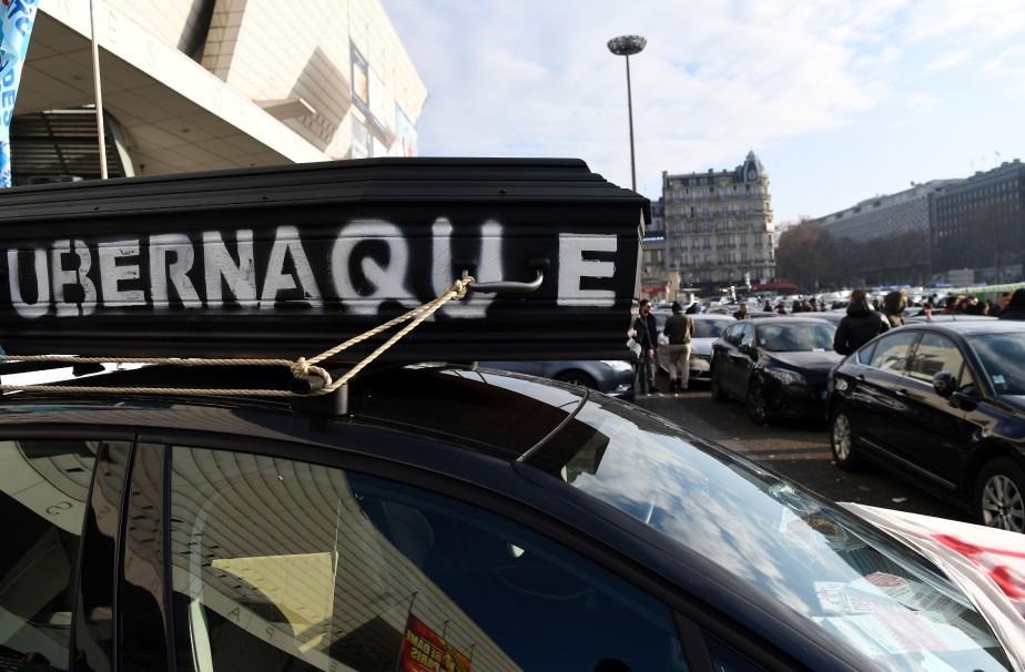 Un faux cercueil portant l'inscription Ubernaque, attaché sur le toit d'une voiture, lors d'une manifestation de chauffeurs dénonçant comme une arnaque les conditions de travail d'Uber.<br /><br /> (AFP)