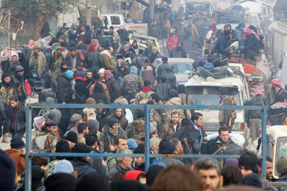 Des civils et des combattants rebelles attendent d'être... (photo Abdalrhman Ismail, REUTERS)