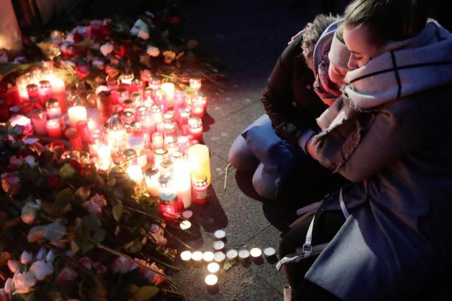 Deux femmes se recueillent devant un mémorial installé... (PhotoMarkus Schreiber, Associated Press)