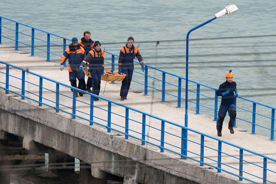 Des sauveteurs ramènent un corps récupéré en mer...