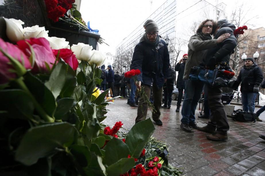 Un caméraman qui pleure la mort de collègues est réconforté par un homme. (PHOTO REUTERS)