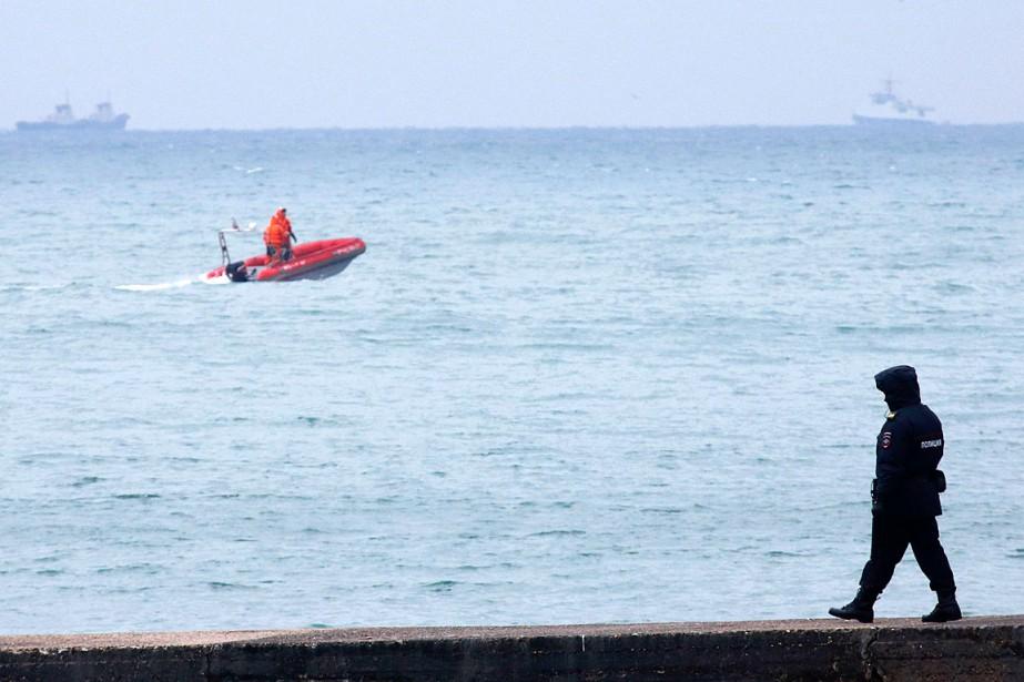 Un policier marche sur le quai alors qu'un bateau s'éloigne pour aller participer aux recherches. (PHOTO REUTERS)