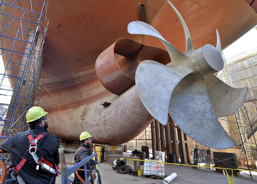 Deux ouvriers de la Davie admirent l'hélice à six pales de l'imposant navire marchand MS Asterix, d'un poids de 20 000 tonnes. Le chantier maritime de Lévis a obtenu le mandat de le transformer en ravitailleur pour la marine canadienne. (Le Soleil, Patrice Laroche)