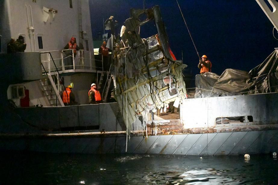 Des employés d'un ministère russe remontent des fragments... (Vladimir Velengurin, Emergency Situations Ministry Photo via AP)