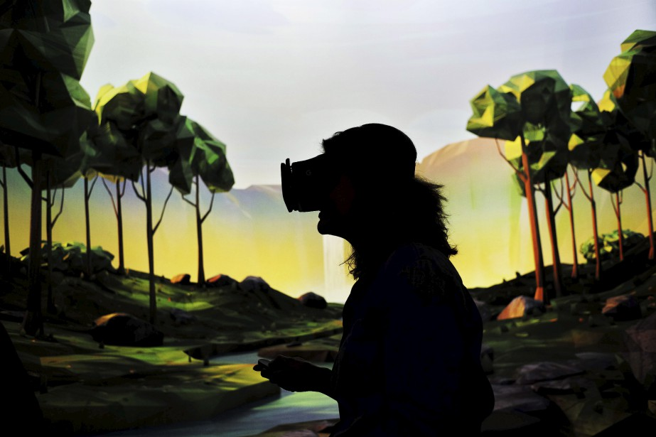 Une femme essaie le système de réalité virtuelle... (AFP)
