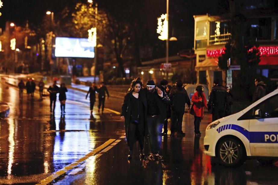 Des jeunes quittent le bar où un homme, apparemment déguisé en père Noël, a ouvert le feu pendant les célébrations du Nouvel An. (AP, Halit Onur Sandal)