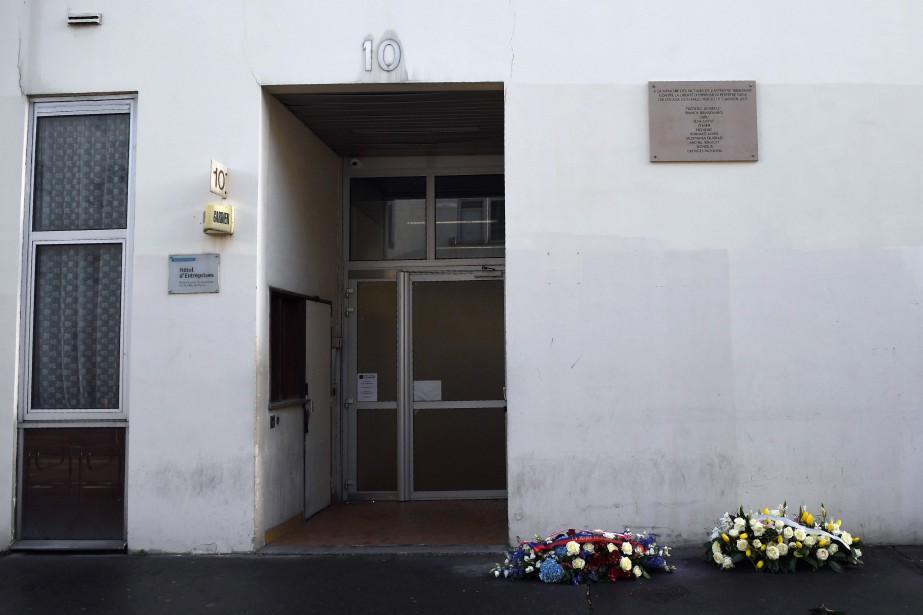Des fleurs sont déposés devant l'ancien local de... (Photo Eric Feferberg, Agence France-Presse)