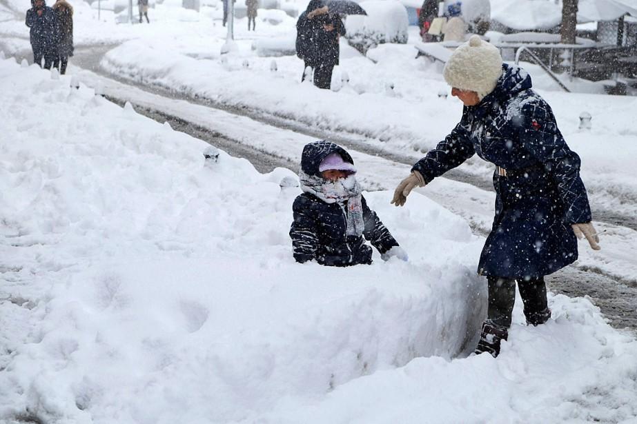 Un enfant s'amuse dans la neige sous le... (Photo Mike Gorder, AP)