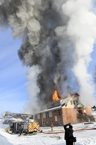 L'incendie de l'immeuble où logeaient plusieurs organismes communautaires a sonné l'alarme générale vers 7h45. Une quarantaine de pompiers tentaient toujours d'éteindre le brasier, samedi après-midi. Leur travail a été compliqué par le temps très froid. (Photo Le Progrès-Dimanche, Rocket Lavoie)