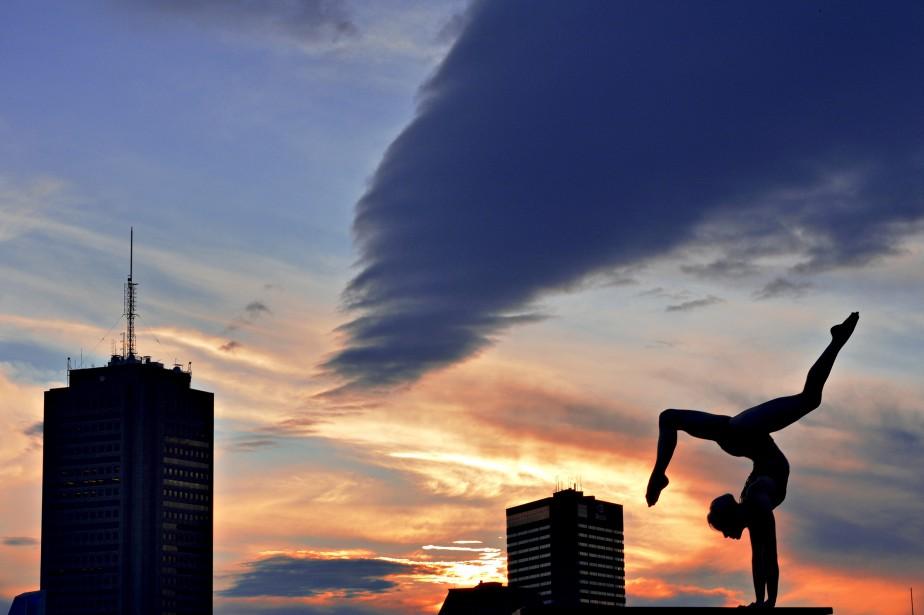 Pascal Ratthé avait en tête de revisiter la classique photo de silhouette au coucher de soleil lorsqu'il a invité une amie artiste de cirque à le joindre pour une session photo. Le photographe a patiemment attendu le parfait instant du coucher de soleil, quand le rouge et l'orangé commencent à se mêler au ciel derrière le complexe G et l'hôtel Delta, pour croquer son cliché. Données techniques : Nikon D4. Focale 90 mm, ISO 800, ouverture F22, vitesse 1/125 e  seconde | 15 janvier 2017