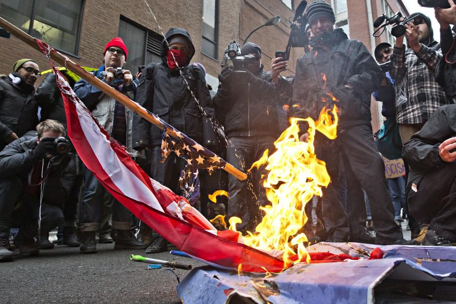 Les manifestants brûlent un drapeau des États-Unis et une mascotte de Donald Trump devant le consulat américain à Montréal. (PHOTO PATRICK SANFAÇON, LA PRESSE)