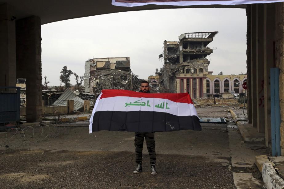 Un étudiant devant l'université de Mossoul, endommagée par... (Photo Khalid Mohammed, Associated Press)
