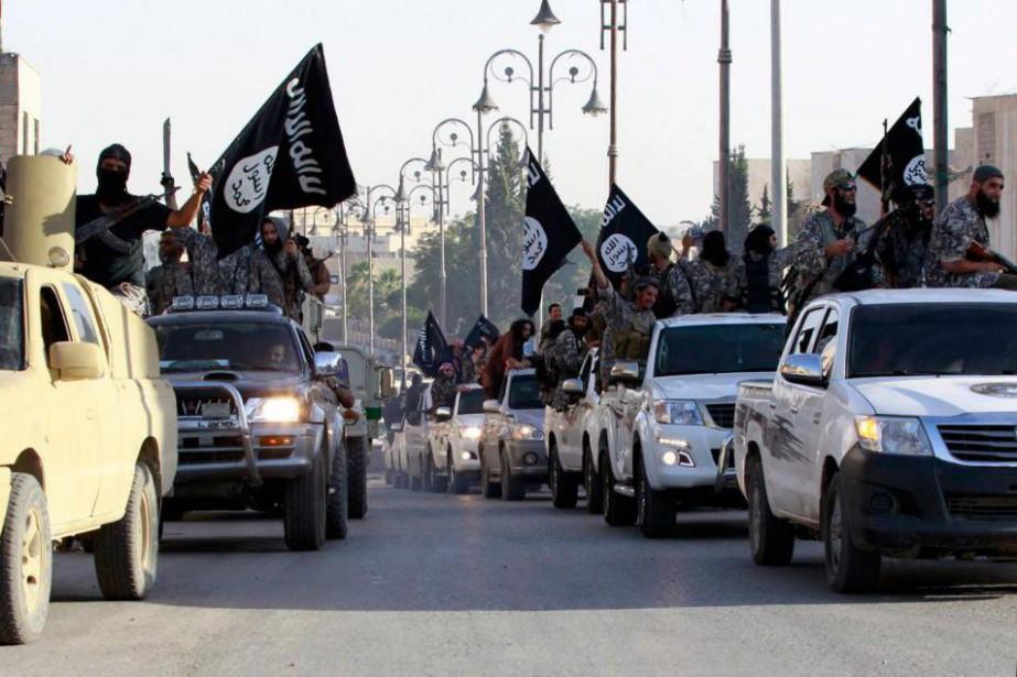 Des combattants du groupe armé État islamique paradent... (Photo archives Reuters)